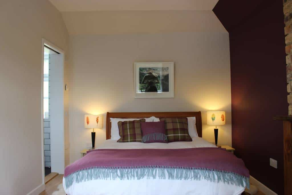 Brae cottage double bed with checked cushions and warm throw