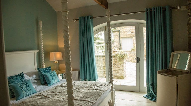 The treehouse bedroom with four poster detail and hidden dressing table