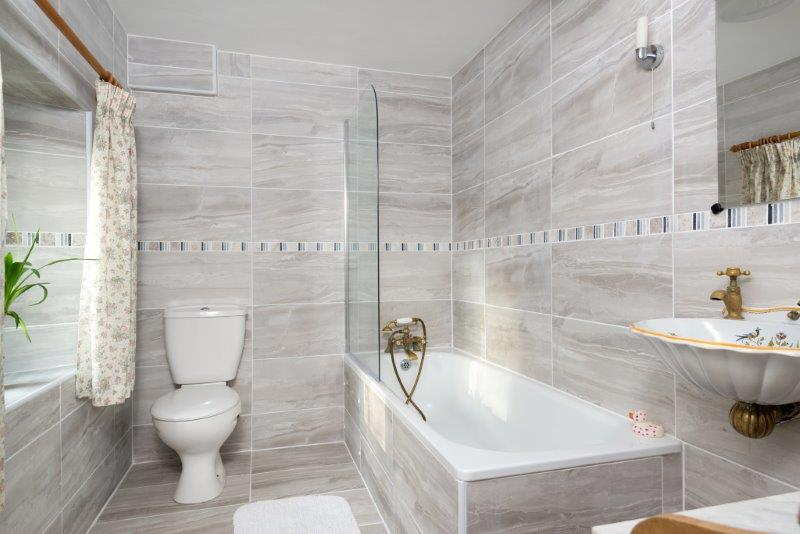Spacious bathroom with grey tiles and vintage basin