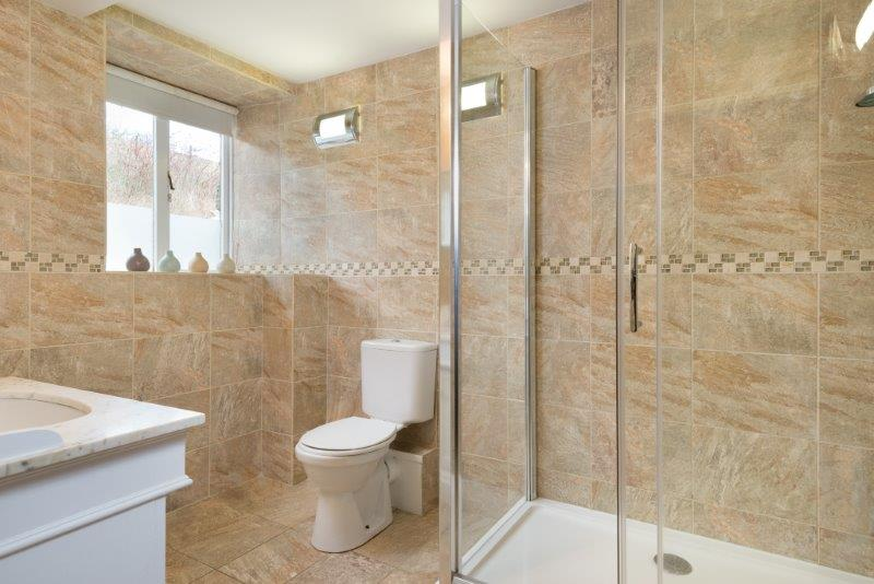 Large bathroom with walk in monsoon shower in neutral colours
