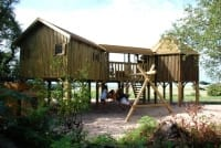 Treehouse with swings and surrounding garden